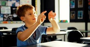 假装的男小学生接触一个无形的屏幕在教室4k 影视素材