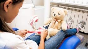 假装逗人喜爱的女孩的特写镜头的图象使用与玩具熊和是牙医 库存图片