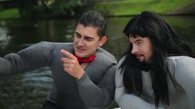假身体肌肉服装的滑稽的活跃人在浮动木筏跳舞并且唱歌 影视素材