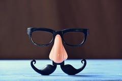 假髭、鼻子和镜片蓝色表面上 免版税库存照片