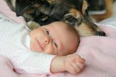 偎依与爱犬的愉快的新出生的婴孩 免版税库存照片