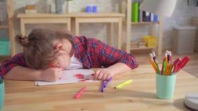 偏僻的儿童孤独性或有精神障碍的画象,画坐在桌上 影视素材