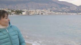 偏僻的冷的海滩的妇女 白种人妇女投掷的石头画象到风平浪静里 股票视频