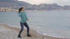 偏僻的冷的海滩的妇女 白种人妇女投掷石头入风平浪静 影视素材