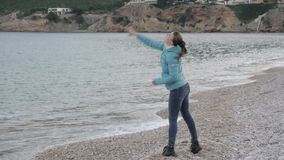 偏僻的冷的海滩的妇女 白种人妇女投掷石头入风平浪静 股票视频