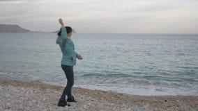 偏僻的冷的海滩的妇女 白种人妇女投掷石头入风平浪静 股票录像