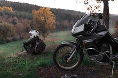 偏僻的概念,人单独坐和神色在距离 冒险摩托车,摩托车骑士,摩托车司机看, 免版税库存照片