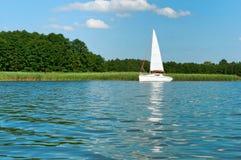 偏僻的白色游艇,在湖的一条游艇在夏天,有白色风帆的一条游艇 免版税图库摄影