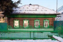 偏僻的绿色原木小屋在冬天站立 免版税图库摄影