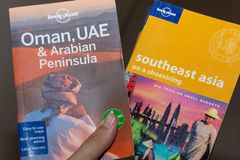 偏僻的行星旅行书在手中阿曼、阿拉伯联合酋长国和阿拉伯半岛和亚洲东南部 库存照片