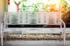 偏僻的长凳、路和早晨阳光 免版税图库摄影