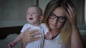 偏头痛,有拿着在手上的头疼的年轻母亲哭泣的孩子户内 股票录像