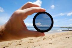 偏振滤光镜举行反对给清晰的海滩 免版税库存照片