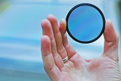 偏振滤光镜在手中 照片的偏振镜反对天空 免版税图库摄影