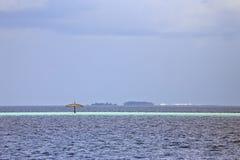 偏僻的伞在海洋 库存照片
