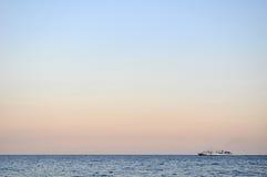 偏僻的小船在背景的风平浪静 免版税库存照片