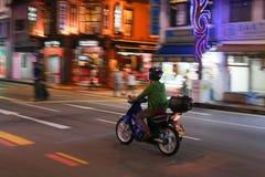 偏僻的摩托车骑士乘驾穿过城市 库存图片