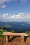 偏僻的椅子有Chiangm草、山和多云天空景色  免版税库存照片
