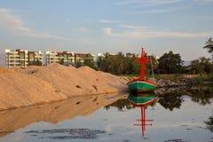 偏僻的渔夫小船的反射在肮脏的水中 图库摄影