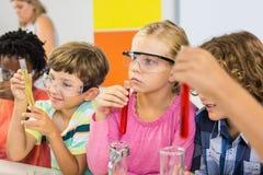 做一个化工实验的孩子在实验室 免版税库存照片