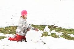 做一个大雪球的女孩 免版税库存照片
