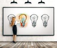 做一个完善的电灯泡剪影的女孩 免版税库存图片