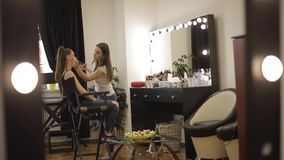 做一个年轻红头发人女孩的美丽的女性化妆师构成坐在大前面的发廊的 股票录像