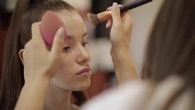 做一个年轻红头发人女孩的美丽的女性化妆师构成坐在大前面的发廊的 影视素材