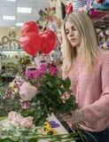 做一个欢乐的花束女孩卖花人的过程 库存图片