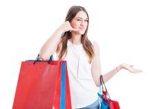 做一个电话姿态用手的购物的正面女孩 免版税库存照片