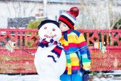 做一个雪人的滑稽的孩子男孩在冬天 免版税库存照片