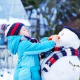 做一个雪人的滑稽的孩子男孩在冬天 免版税库存图片