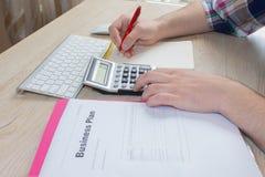 做一些文书工作的商人使用他的计算器 拿着圆珠笔的商人手研究计算机,运作的onlin 免版税库存图片