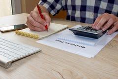 做一些文书工作的商人使用他的计算器 拿着圆珠笔的商人手研究计算机,运作的onlin 库存图片