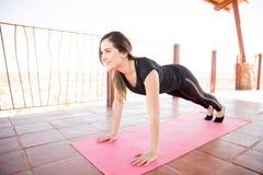做一些瑜伽的坚强的妇女 免版税库存图片