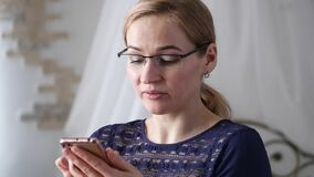 做一份视频通信在智能手机与朋友的白肤金发的女实业家 慢的行动 股票录像