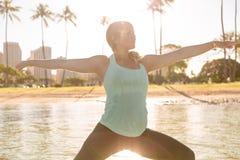 做一口瑜伽的妇女在威基基在日出战士姿势 免版税图库摄影