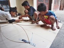 做一只传统风筝的巴厘语男孩 免版税库存照片