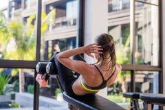 做一名运动的妇女的画象行使abdominals在豪华旅馆制定出在健身房在夏天 库存图片