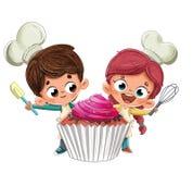 做一块愉快的杯形蛋糕的孩子 免版税库存照片