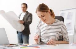 做一张图画的高兴女性工程师在办公室 免版税库存照片