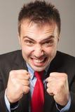 做一张恼怒的面孔的愤怒的商人 库存照片