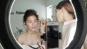 做一种发型在演播室和拍在电话的年轻美丽的妇女照片 股票视频