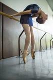 做一种锻炼的年轻舞蹈家在教室在纬向条花附近 Stret 免版税图库摄影