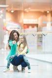 年轻做一起购物的母亲和她的女儿 免版税图库摄影