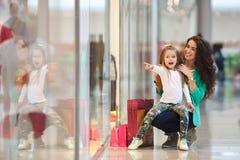 年轻做一起购物的母亲和她的女儿 免版税库存图片