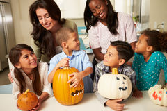 做万圣夜灯笼的母亲和孩子 免版税库存图片