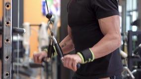 做三头肌的年轻适合的肌肉人关闭拉下绳索引伸锻炼在现代健身俱乐部 股票录像