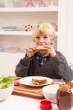 做三明治的男孩厨房 免版税库存图片