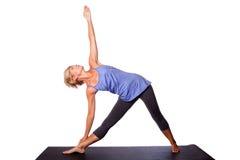 做三角瑜伽姿势的美丽的妇女 库存图片